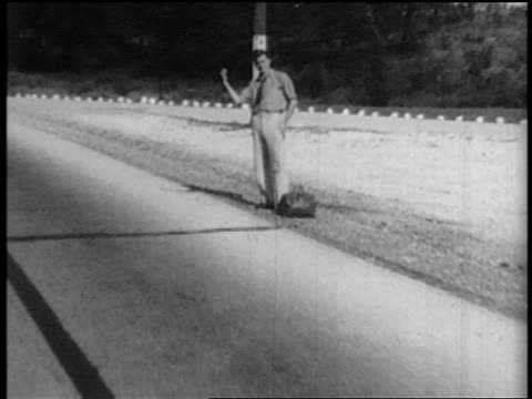 CAR point of view man with thumb raised hitchhiking alongside highway
