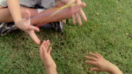 Point of view medium shot two children sitting in grass and playing cat's cradle string game