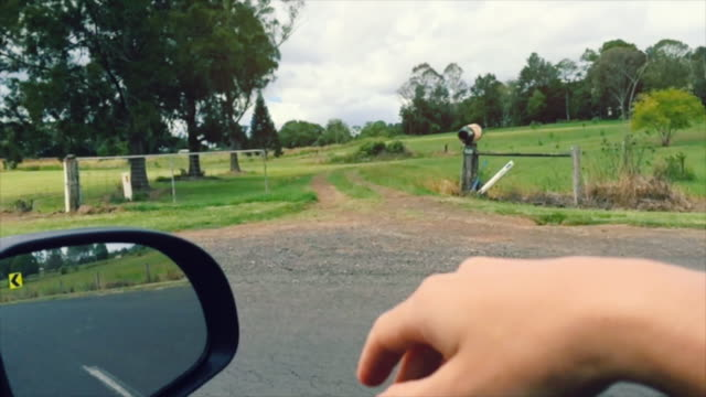 Point of View (POV) of a hand waving into the wind in a car with a green landscape, in slow motion, Byron Bay