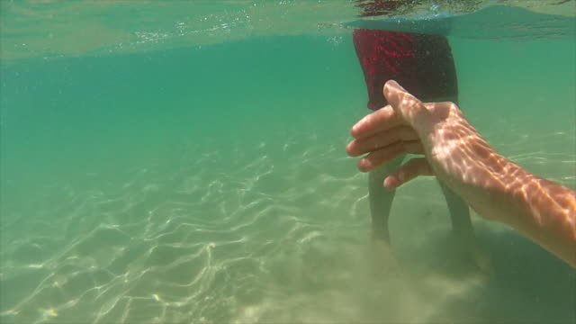 Point of View (POV) of a woman swimming at Byron Bay with his partner looking at her