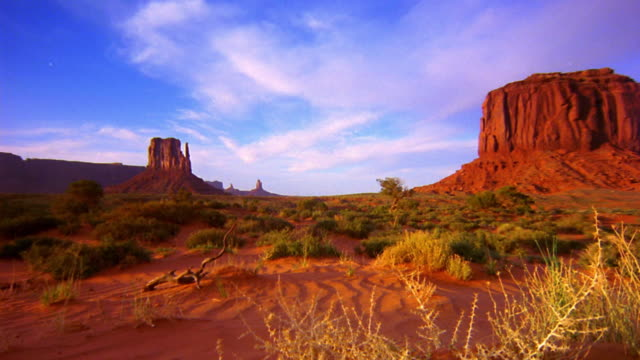 point of view over desert floor with plants + stop / time lapse clouds + buttes in distance / Monument Valley, USA