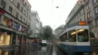 Point of view shots filmed from the rear of a tram carriage during journey along city streets between station stops on a rainy day in Zurich...