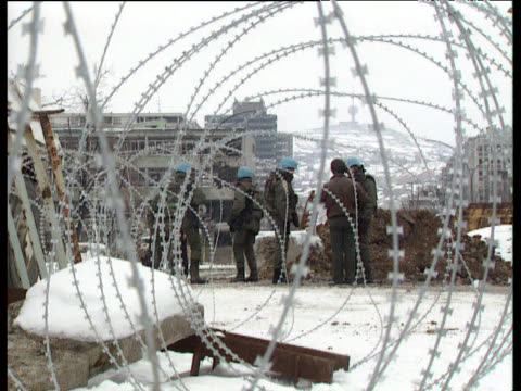 Point of view through frosted barbed wire of UN soldiers keeping watch Sarajevo 1995