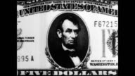 / Pointer indicates presidential portrait on five dollar bill / CU President George Washington portrait on one dollar bill / CU President Thomas...
