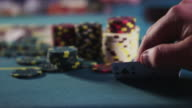 Poker chips stacked on a gambling table; a hand reaches in and sneaks a look at two (2) cards - ace of spades and eight of spades.