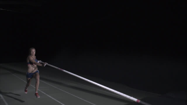 A pole vaulter narrowly clears the bar.