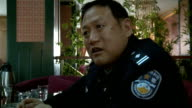 Police accuse superiors of corruption INT GVs police officers sitting around some in uniform Liang Min Zhen interview SOT in the past tried to stop...