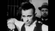 / Police and cuffed criminals walk out of a building / CU John Dillinger / man points out bullet holes on a car / Dillinger's booking photo / several...