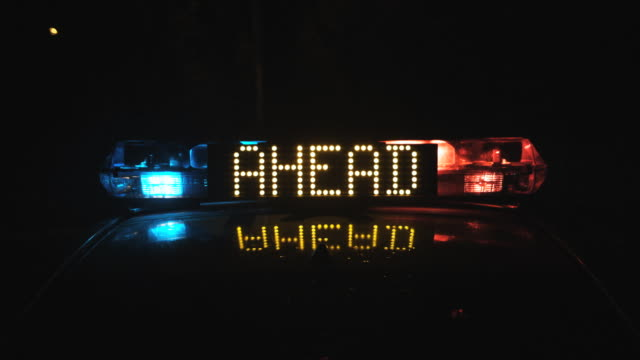 CU Police car emergency lights flashing at night, 'Accident ahead' sign, Auckland, New Zealand