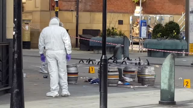 A police cordon remains in place and police vans are at the scene Beer barrels inside the cordon have what appears to be police riot shields placed...