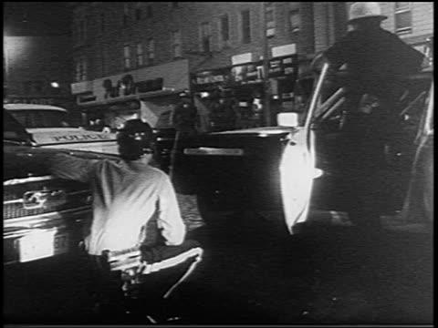 B/W 1967 police crouching behind car on street at night / Newark race riots New Jersey / newsreel