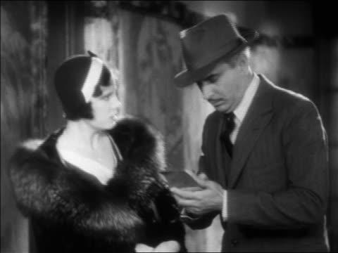 B/W 1931 police detective (Eddie Kane) interviewing Irene Dunne in hallway / feature