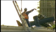 recovery operation continues Worker attaching crane to section of helicopter and it is lifted up and hoisted to ground