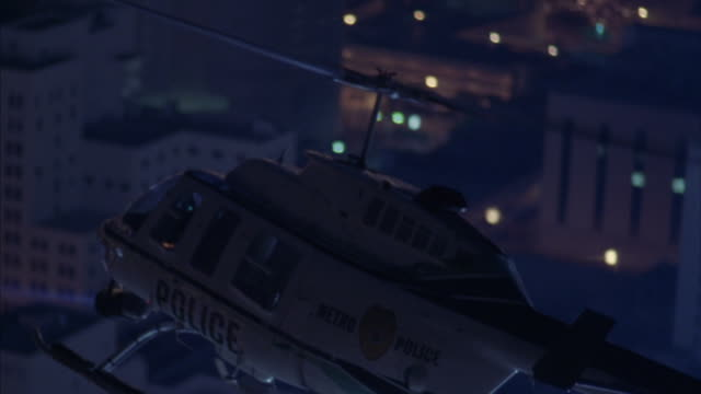 A police helicopter flies over Miami, Florida at night.