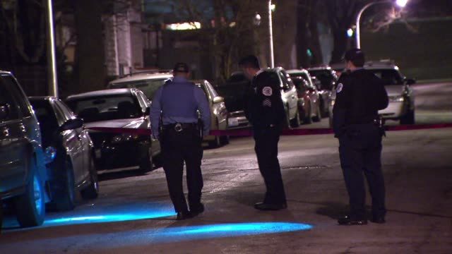 WGN Police investigating crime scene at night using flashlights on December 11 2012 in Chicago Illinois