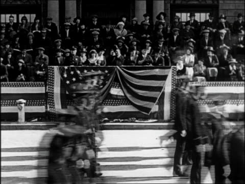 B/W 1922 police marching past dignitaries seated on sidelines in parade / feature
