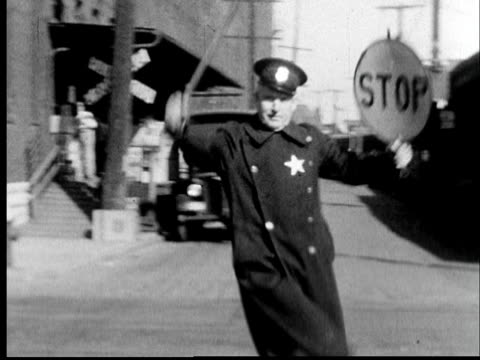 1935 MS Police officer comically directing traffic with stop sign and baton/ St. Louis, Missouri