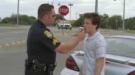 MS TS POV CU Police officer giving alcohol breath test to man standing near car / Elmendorf, Texas, USA