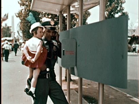 Police officer holding lost little girl in his arms making phone call from emergency phone booth at New York World's Fair/ CU Policeman on phone/...