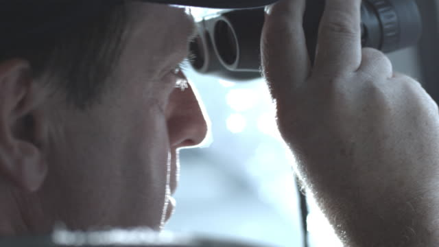 ECU, SHAKY, Police officer looking through binoculars sitting in police van, Staten Island, New York City, New York State, USA