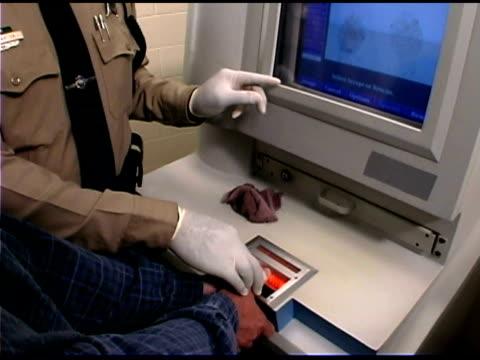 Police officer putting fingerprints on computer