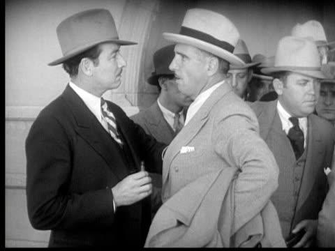 1931 B/W MS Police officer removing handgun from gangster's inner jacket pocket/ Los Angeles, California, USA/ AUDIO