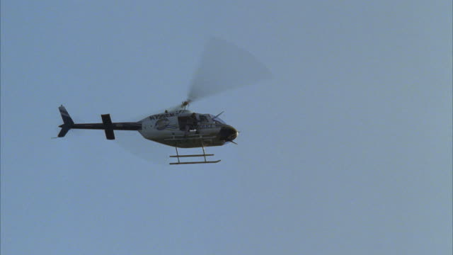 LA, TS, MS, Police officer sitting in open helicopter door, helicopter flying against clear sky
