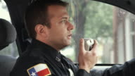 MS ZI ZO Police Officer sitting in police car talking on CB radio / Dallas, Texas, USA