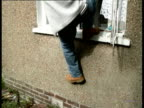 Police officer smashing window PAN LR other officers making forced entry into house during drugs bust / CBV officers pushing into flat during drugs...