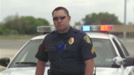 MS Police officer standing and crossing his arms in front of police car / Elmendorf, Texas, USA