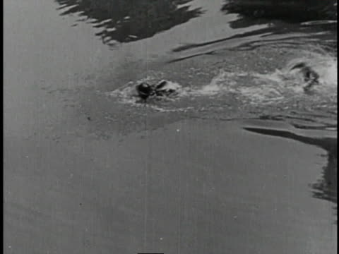1920 MONTAGE Police officer swimming after man in pond and crawling on belly onto land to continue the chase