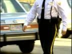 1996 MS Police officer walking across city street / Washington, DC, USA