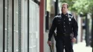 MS PAN TD Police officer walking down sidewalk / Dallas, Texas, USA