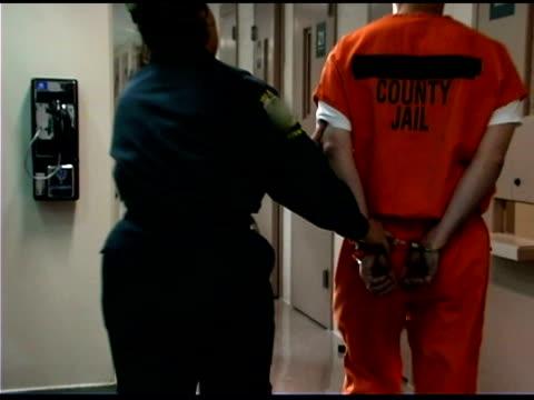 Police officer walking prisoner to cell