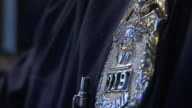 A police officer wears a badge and several medals on a jacket.