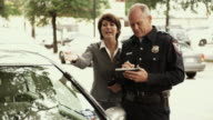 MS Police officer writing parking ticket, woman arguing with police officer / Dallas, Texas, USA