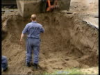 Police officers and workmen with mechanical digger excavating car park in the hunt for the remains of IRA victim Jean McConville ZOOM IN daughters of...