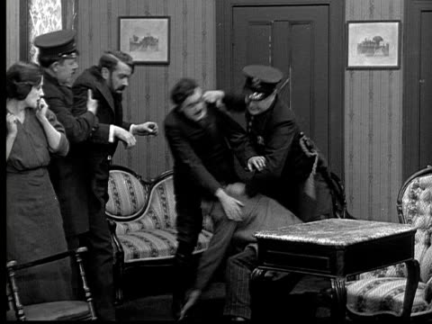 B/W, MS, Police officers breaking up fight, man pulling off fake moustache, 1924