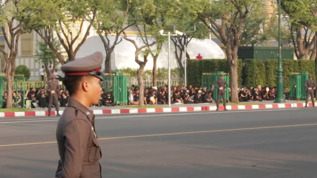 Police officers stand guard as mourners wait ahead of the cremation of the late King Bhumibol Adulyadej in Bangkok Thailand on Thursday Oct 26...