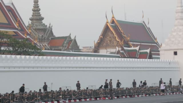 Police officers stand guard as mourners wait outside the Grand Palace at Sanam Luan ahead of the cremation of the late King Bhumibol Adulyadej in...