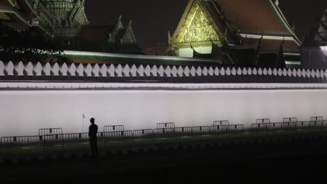 Police officers stand guard outside the Grand Palace at Sanam Luan ahead of the cremation of the late King Bhumibol Adulyadej in Bangkok Thailand on...
