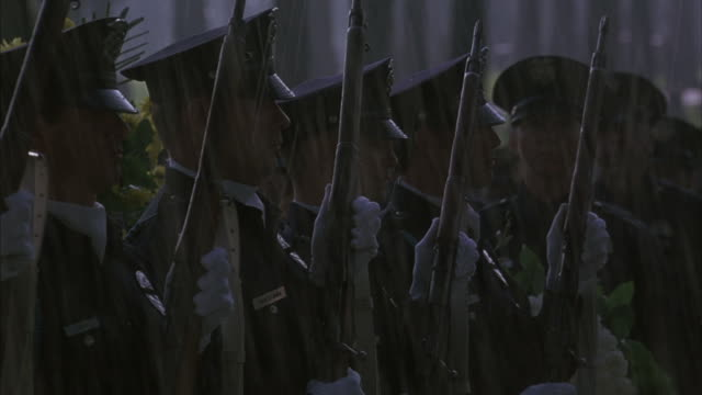 Police officers stand in the rain and with guns held high perform a 21-gun salute.