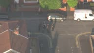 Aerials AIR VIEW cordonedoff street / bomb disposal robot / police car blocking road / crowd of evacuated residents in street