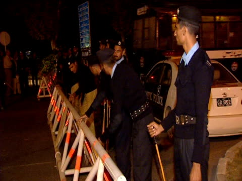 Police standing by barricades at night