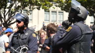 Police surround a counter protester who was arrested while protesting against Trump supporters in Martin Luther King Park in Berkeley California...