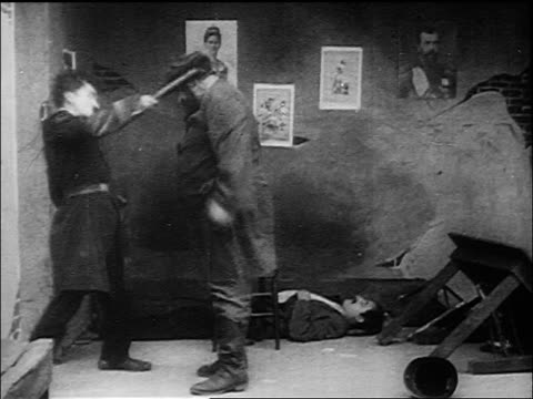 B/W 1917 policeman Charlie Chaplin fighting large man climbing man to reach manhole above
