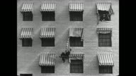 Policeman chases fleeing Buster Keaton upstairs before Keaton exits through window and uses ripped awnings to swing from one to another to reach the ground