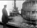 Policeman standing on dock Tugboat escorting doubledecker boat into harbor WS Police officers man in bowler hat waving from dock
