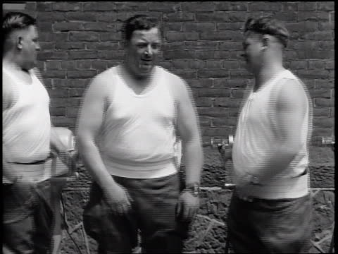 B/W 1935  3 policemen in tank tops standing + turning with vibrating straps on bellies / newsreel