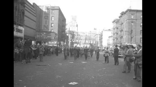 Policemen restraining angry people in street / VS crowd of angry shouting people on sidewalk being held back by policemen / people holding banner...